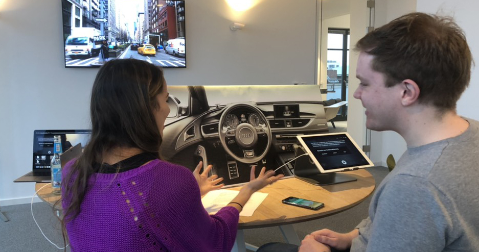 Picture of the user-test set-up, 2 people looking at a prototype of a car dashboard.
